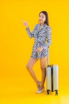 Портрет красивая молодая азиатская женщина с паспортом багажа и посадочным талоном на желтом