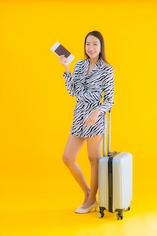Portrait beautiful young asian woman with travel luggage passport and boarding pass on yellow