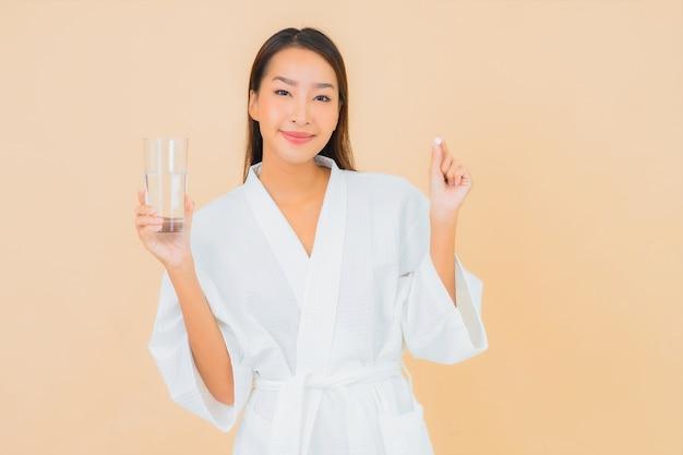 Женщина портрета красивая молодая азиатская с стеклом воды и пилюлькой лекарства на бежевом