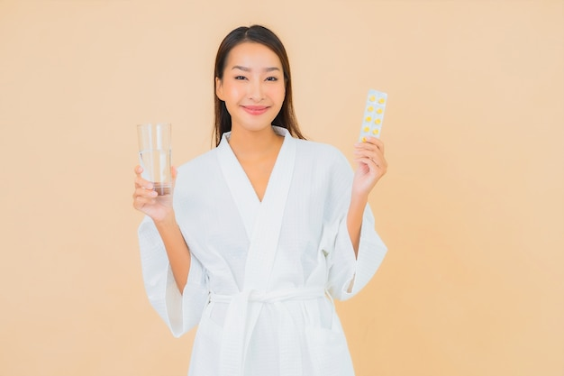 Portrait beautiful young asian woman with water glass and drug pill on beige
