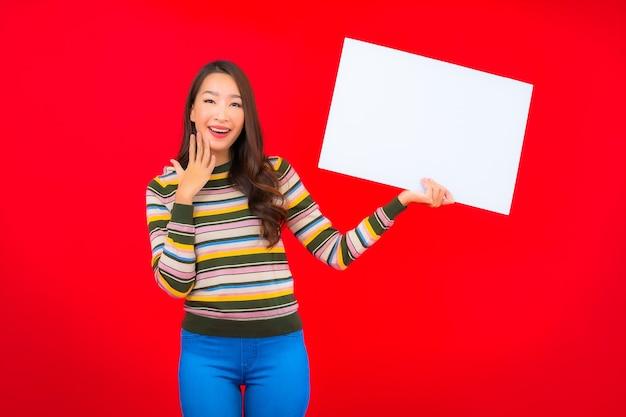 Bella giovane donna asiatica del ritratto con il tabellone per le affissioni vuoto bianco sulla parete rossa