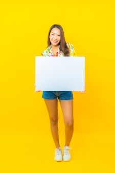 Portrait of beautiful young asian woman with white empty billboard on yellow wall