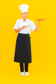 Женщина портрета красивая молодая азиатская с деревянной разделочной доской на желтом изолированном фоне