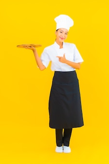 Portrait beautiful young asian woman with wooden cutting board on yellow isolated background