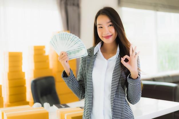 肖像画の美しい若いアジアの女性は自宅でラップトップの現金と段ボール箱をオンラインで発送する準備ができて仕事します。