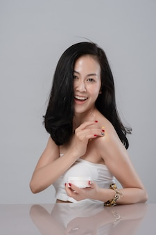 Portrait of beautiful young asian woman wrapped in towel spreading cream on her shoulder.