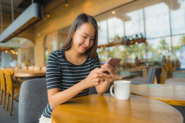 Belle giovani donne asiatiche del ritratto nel caffè e nel ristorante della caffetteria con il telefono cellulare