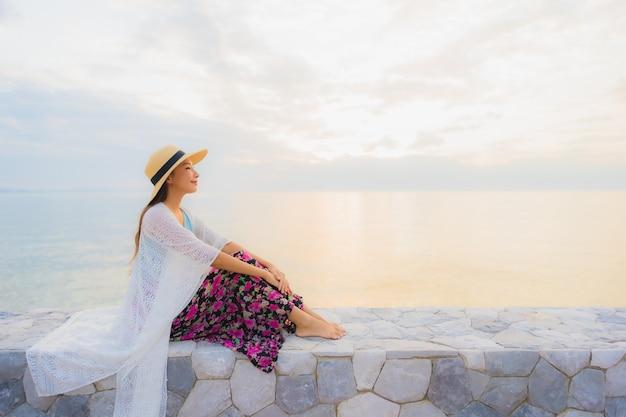 幸せな笑顔の美しい若いアジア女性の肖像画は海ビーチ海の周りリラックスします。