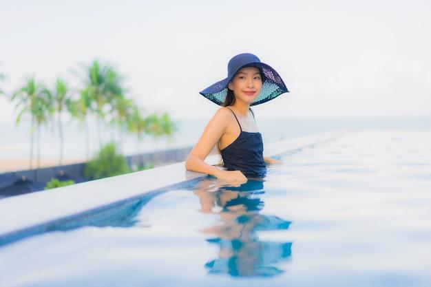 肖像画美しい若いアジア女性の幸せな笑顔は、ホテルの屋外スイミングプールをリラックスします。