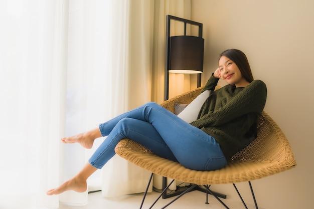 초상화 아름 다운 젊은 아시아 여성 행복 한 미소는 소파의 자에 앉아 휴식