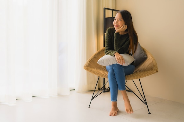 Portrait beautiful young asian women happy smile relax sitting on sofa chair