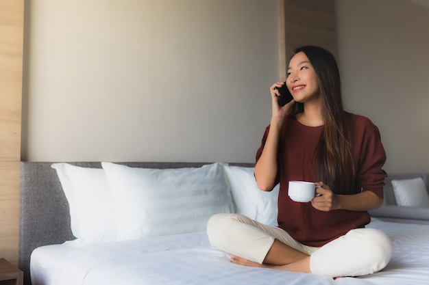 Portrait beautiful young asian women happy smile with coffee and mobile phone