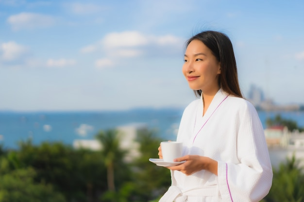 Portrait beautiful young asian women hold coffee cup in hand around outdoor view