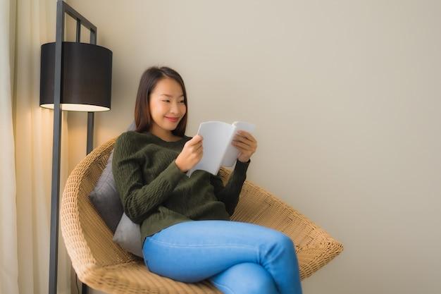 세로 아름다운 젊은 아시아 여성 책을 읽고 소파 의자에 앉아