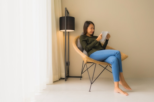 Portrait beautiful young asian women reading book and sitting on sofa chair