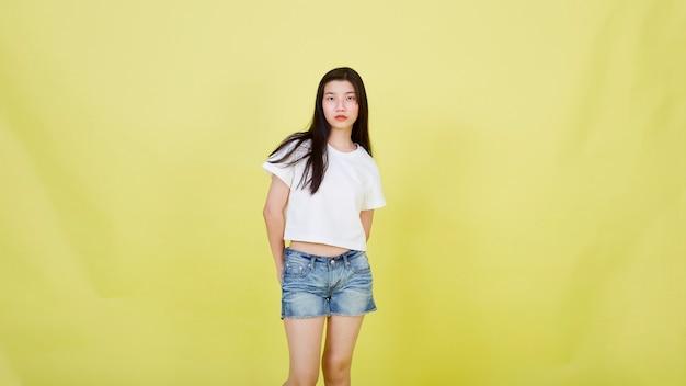 Портрет красивых молодых азиатских женщин в повседневной летней одежде на желтом фоне