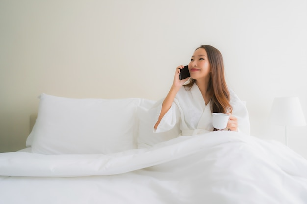 Portrait beautiful young asian women with coffee cup and mobile phone on bed
