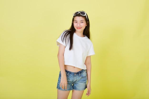 Портрет красивых молодых азиатских женщин с очками на голове на желтом фоне
