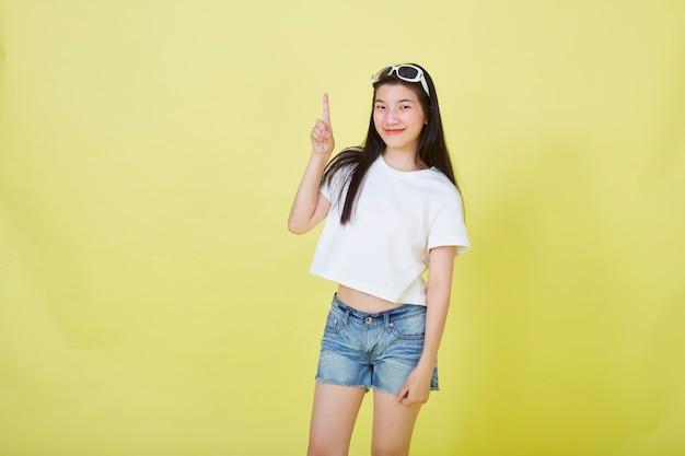 Портрет красивых молодых азиатских женщин с очками на голове, указывая вверх на желтом фоне