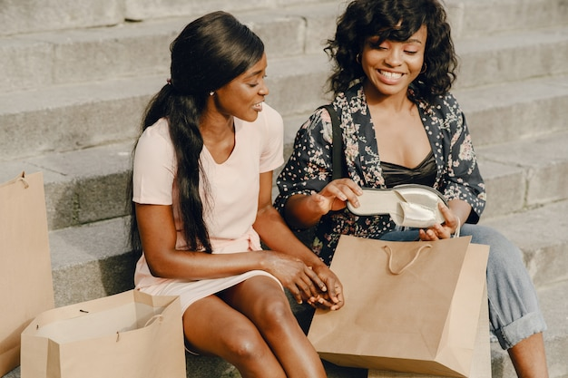 Portrait of beautiful young black women with shopping bags