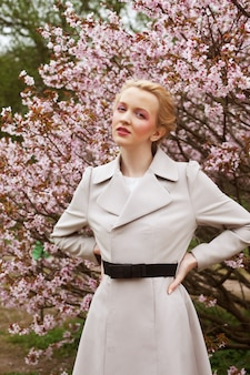 Portrait of a beautiful young blond woman on a background of pink cherry blossoms in spring