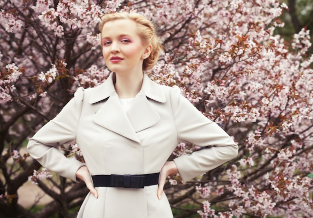 Portrait of a beautiful young blond woman on a  of pink cherry blossoms in spring