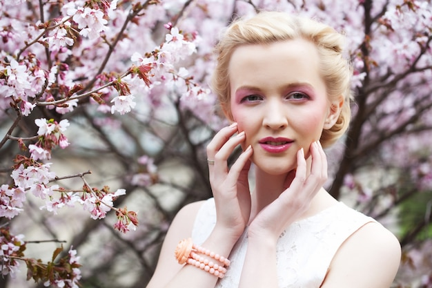 Portrait of a beautiful young blond woman  of pink cherry blossoms in spring