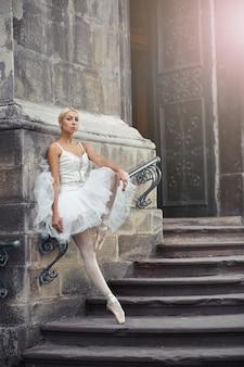 Ritratto di una bellissima giovane ballerina bionda in abito bianco in piedi con grazia sulle scale di un vecchio castello.