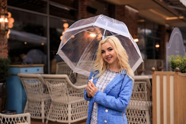 Portrait of beautiful young blonde woman holding a see through umbrella in the rain on a city street