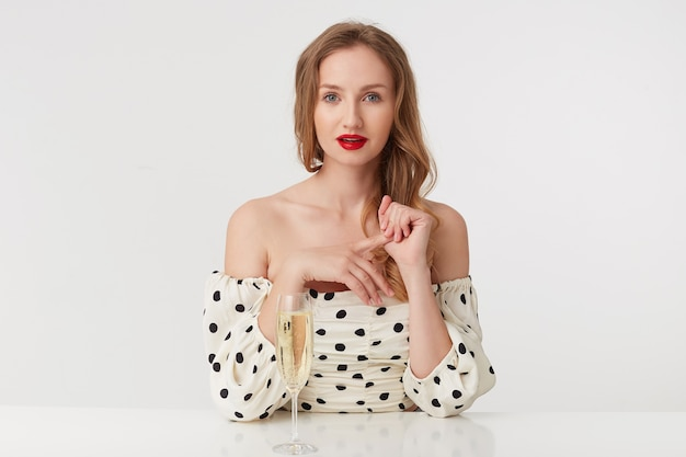 Portrait of a beautiful young blue-eyed blonde with red lips in a polka-dot dress. siting at the table with a glass of champagne. isolated over white background.