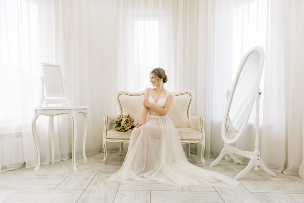 Portrait of a beautiful young bride in a bright room in a romantic atmosphere. bride in a negligee with a wedding bouquet
