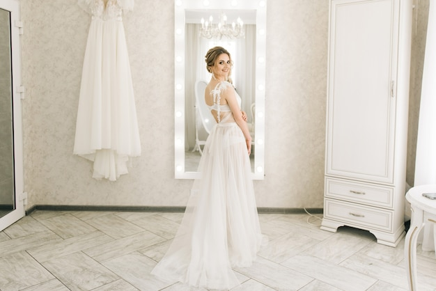 Portrait of a beautiful young bride in a bright room in a romantic atmosphere. bride in a negligee with wedding hair and makeup