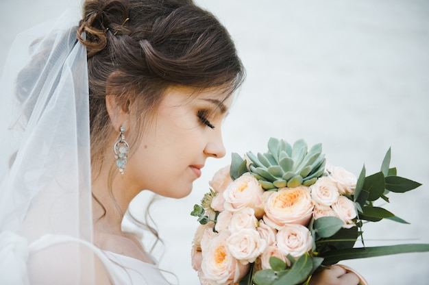 Portrait of a beautiful young bride with a bouquet on a white background. wedding.