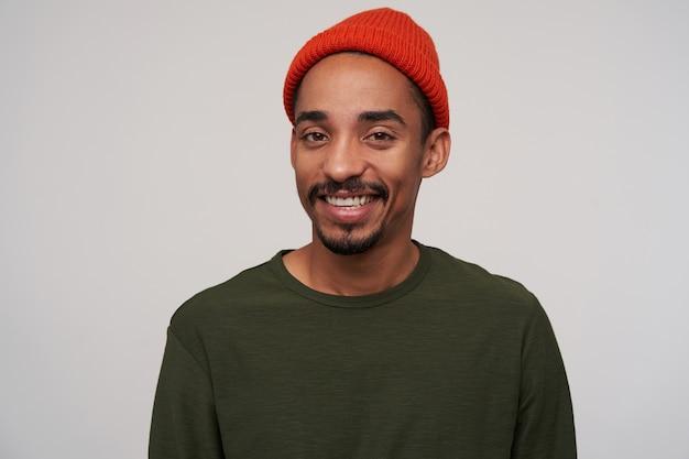 Ritratto di bello giovane maschio dalla pelle scura dagli occhi marroni con la barba che guarda allegramente con un sorriso piacevole, vestito con cappello rosso e pullon kaki su bianco