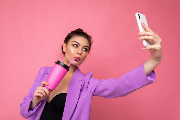 Portrait of a beautiful young brunet woman in fashionable purple suit on a pink background in studio in a holding a popular phone and taking selfie photo and drinking through a straw beverage