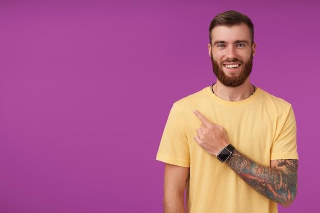 Ritratto di giovane e bella bruna maschio barbuto con tatuaggi guardando felicemente e sorridendo sinceramente, mostrando verso l'alto con l'indice, isolato su viola