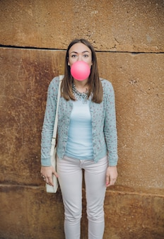 Portrait of beautiful young brunette teenage girl blowing pink bubble gum over a stone wall background