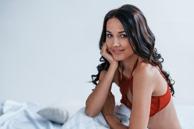 Portrait of beautiful young brunette that is in red underwear sitting on the bed.