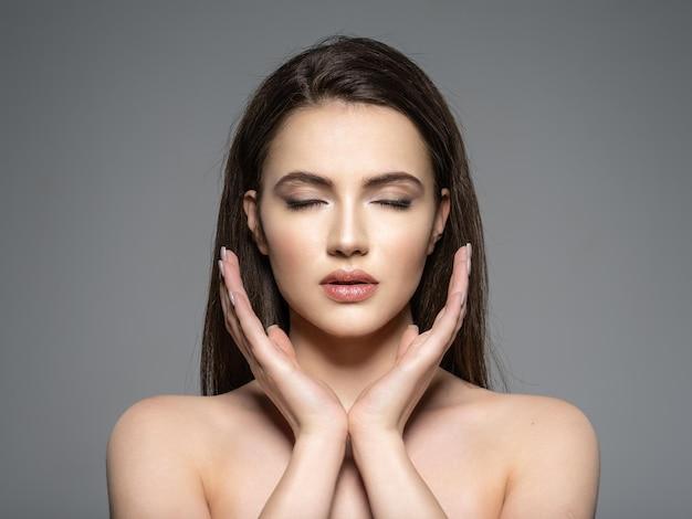Ritratto di giovane e bella donna bruna con viso pulito. faccia calma. modello grazioso con gli occhi chiusi. meditazione
