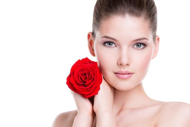Ritratto di giovane e bella donna bruna con rosa rossa vicino al viso - isolato su bianco.