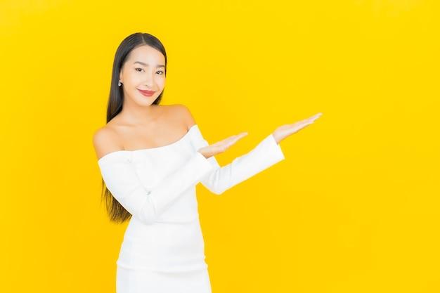 Ritratto di bella giovane donna asiatica di affari che sorride con il vestito bianco sulla parete gialla