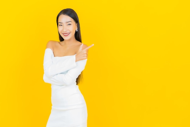 Portrait of beautiful young business asian woman smiling with white dress on yellow wall