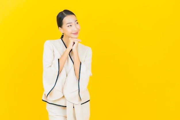 Ritratto di donna asiatica bella giovane impresa sorridente con abito bianco sulla parete gialla