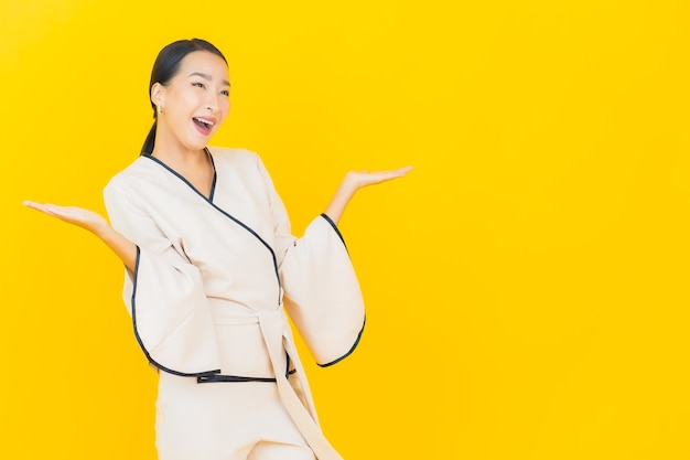 Portrait of beautiful young business asian woman smiling with white suit on yellow wall