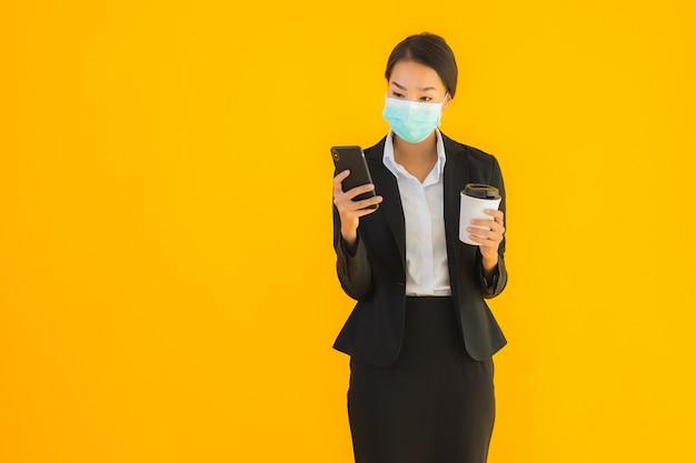Telefono cellulare asiatico di uso della maschera di usura della donna di bei giovani affari del ritratto con caffè