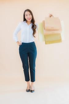 소매 및 백화점에서 쇼핑 가방을 많이 가진 세로 아름 다운 젊은 비즈니스 아시아 여자