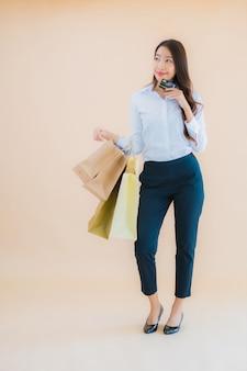 Женщина портрета красивого молодого дела азиатская с много хозяйственной сумкой от розничных продаж и универмага