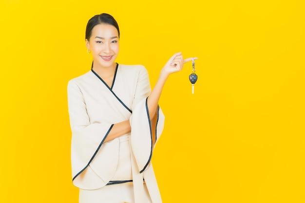 Ritratto di bella giovane donna asiatica di affari con la chiave dell'automobile sulla parete gialla