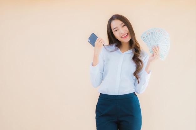 Donna asiatica di bella giovane impresa del ritratto con contanti o soldi