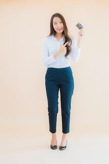 Donna asiatica di bella giovane impresa del ritratto con carta di credito